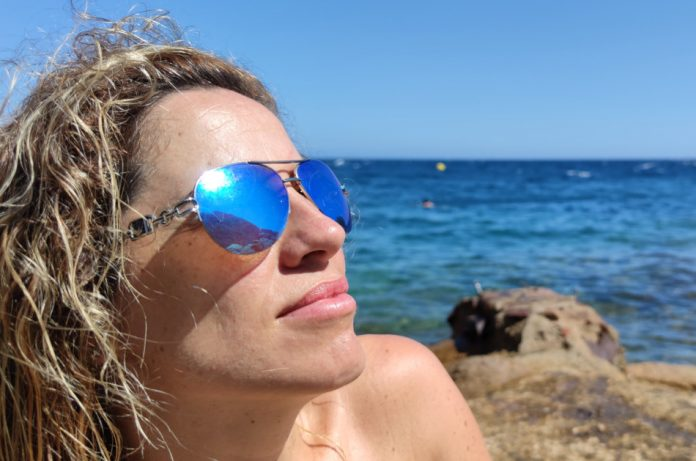 Woman with sun glasses sits by the Mediterranean Sea, sunbathing.