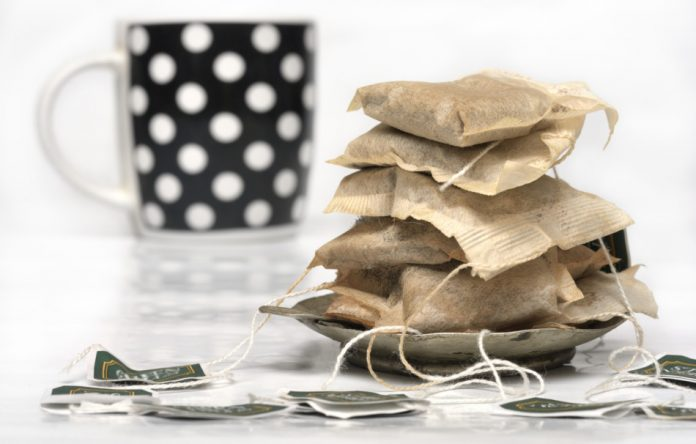 Used tea bags stacked up on a small saucer in front of a black cup with white polka dots.