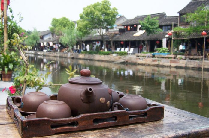 Clay teapot and cups sit on a wooden tray on top of a table next to the scenic waterways in Xitang, one of China's watertowns.