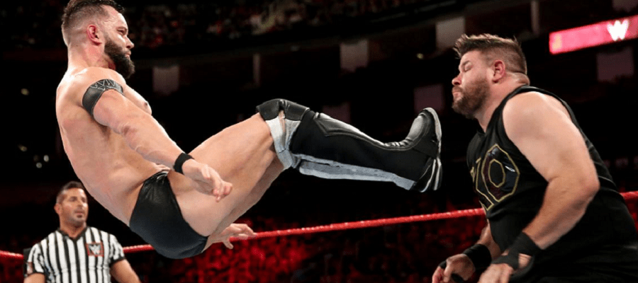Finn Balor dropkicks Kevin Owens