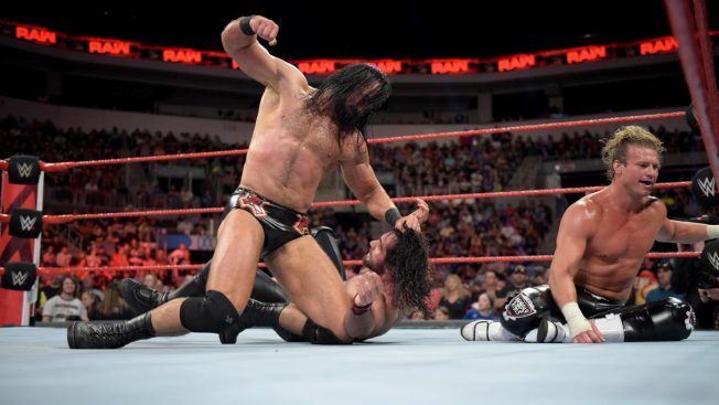 Drew McIntyre punches Seth Rollins while Dolph Ziggler watches