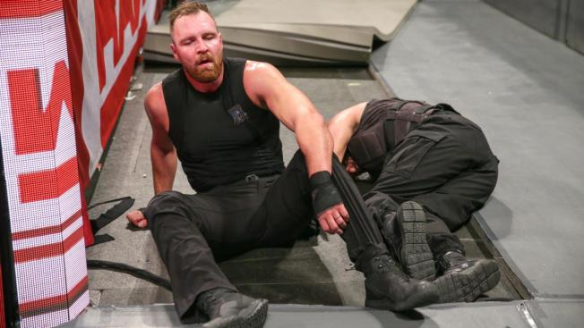 Dean Ambrose sits besdie Seth Rollins after giving him a Dirty Deeds on the concrete