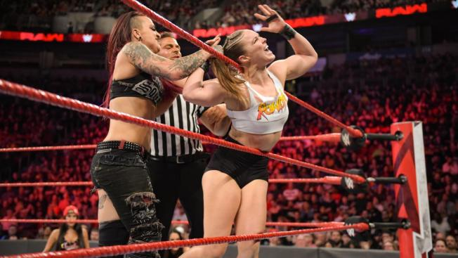 Ruby Riotss bends Rousey over the ropes by her hair