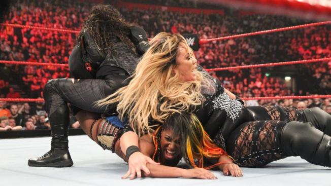 Tamina holds Ember Moon while NIa Jax elbow drops her