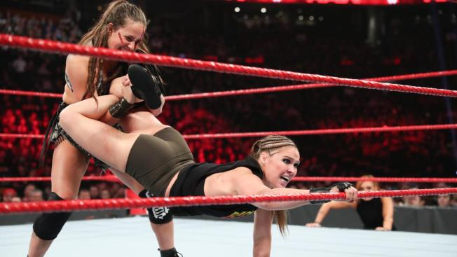 Ronda Rouey reaches for the ropes to free herself from Srah Logan's ankle lock