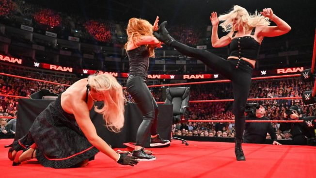 Charlotte Flair kicks Becky Lynch in the face, with Lacey Evans on the mat in front of them,