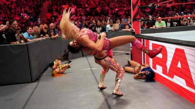 Bayley suplexes Charlotte Flair on the outside, Sasha Banks and Becky Lych are down in the background