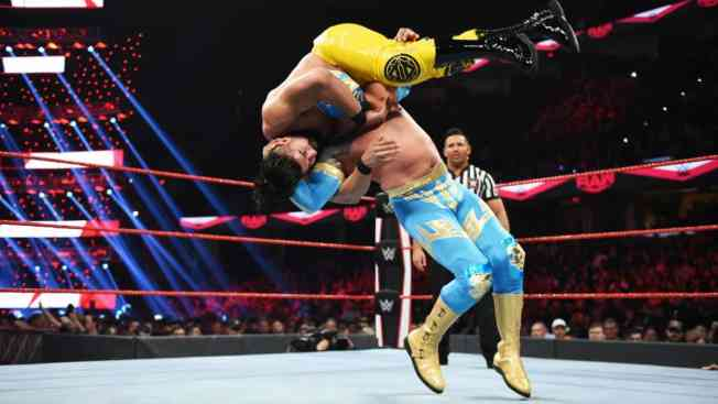 Sin Cara with Andrade on his shoulders