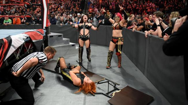 The Kabuki Warriors stand over Becky Lych after putting her through a table