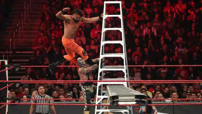Andrade flies off a ladder assisted by Rey Mysterio