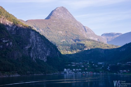 The view of Geiranger village with a mighty Åkerneset in the background. The mountain is slightly eroding and is expected some day to crash down into a fjord, which will create a tsunami - an event that already happened a few times in Norwegian fjords.