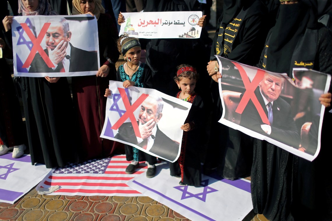FILE - Palestinians step on Israeli and U.S. flags and hold posters of U.S. President Donald Trump and Israeli Prime Minister Benjamin Netanyahu during a protest against Bahrain's workshop for U.S. peace plan, in the Gaza Strip June 18, 2019