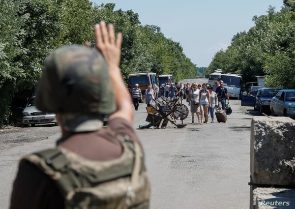 FILE - A member of the Ukrainian State Border Guard Service signals for people to stop as they approach a checkpoint at the contact line between Russia-backed rebels and Ukrainian troops, in Mayorsk, eastern Ukraine, July 3, 2019.