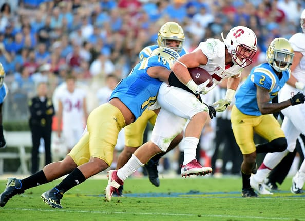 PASADENA, CA - SEPTEMBER 24:  Christian McCaffrey #5 of the Stanford Cardinal is tackled by Josh Woods #19 of the UCLA Bruins on a run during the first quarter at Rose Bowl on September 24, 2016 in Pasadena, California.  (Photo by Harry How/Getty Images)
