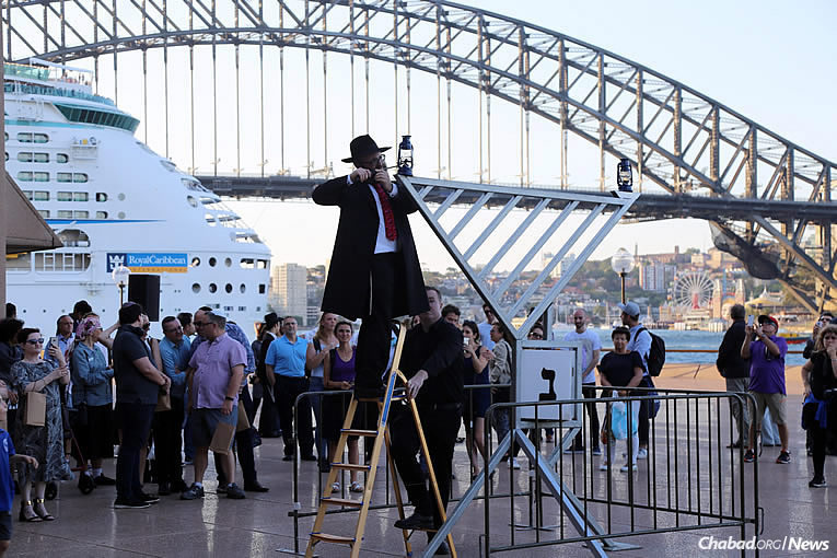 Chabad Rabbi Danny Yaffe lights the menorah at the Sydney Opera House/Harbour in Australia, on Tuesday, Dec. 12, the first night of the eight-day holiday of Chanukah.