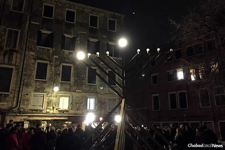 Hundreds of celebrants gather at the public menorah-lighting organized by Chabad-Lubavitch in Campo di Ghetto Nuovo in Venice, Italy, on Tuesday, Dec. 12, the first night of the eight-day holiday of Chanukah.