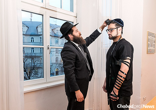 Gordon wraps tefillin with photographer Mitya Kolomiyets. In the background is the building in which Hitler once lived.