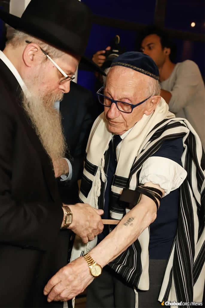 Le rabbin Dovid Weitman aide Andor Stern à mettre des téfilines pour la première fois. Stern est le seul survivant connu de l'Holocauste à être né au Brésil.