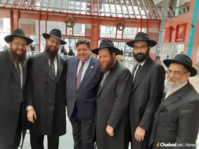 J. B. Pritzker joined the Chabad-Lubavitch rabbi to expose Illinois's official state menorah on 17 December at James R. Thompson Center, where Illinois State government offices are.