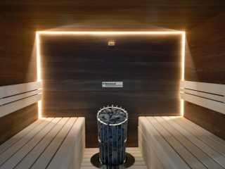 Sauna mit versenkt eingebautem Ofen. Glatten Paneele in Robinie/ Akazie. Bänke in Linde