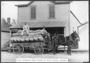 Two men sit atop a wagon loaded with feed in front of the J.W. Andrews Feed Store in Alta Vista, Kansas.