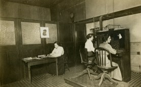 Ruth Pennock, left, and Josie and Alice Smith, seated at the switchboard, work inside the McMahan Telephone Exchange, circa 1900.
