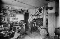 "Seigfried ""Fred"" Herrmann is seen inside his Alma, Kansas shoe repair shop in this Gus Meier view from 1920."
