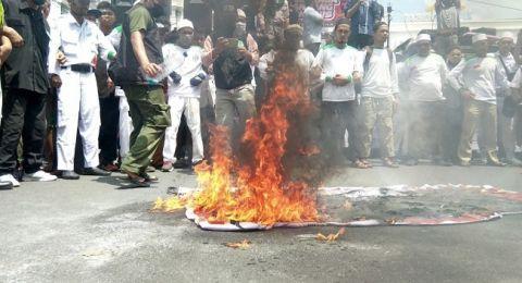 Pembakaran Spanduk Bergambar Babi Bermoncong Putih.(dilangsir suara.com)