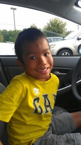 Wearing bright yellow, this school-age child smiles for photo from passenger seat of car