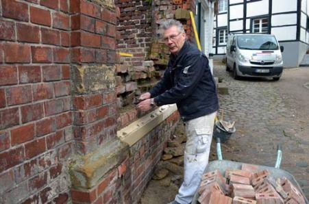 Josef Bücker restauriert die Mauer zum Park der Ev. Kirche.