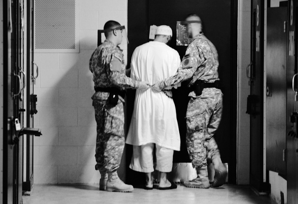 Guards from Camp 5 at Joint Task Force Guantanamo escort a detainee from his cell to a recreational facility within the camp. (Flickr/Kilho Park)