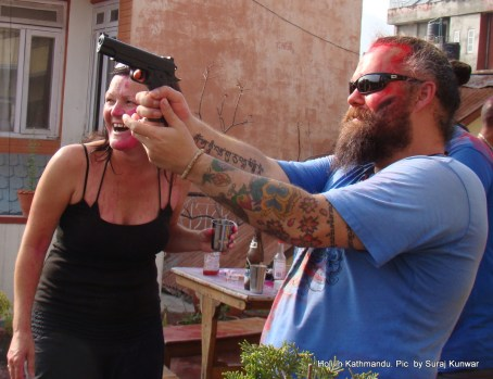 A foreign national points water gun at filmmaker Murray Kerr (not seen in the photo) while celebrating Holi at the rooftop of a hotel in Thamel, Kathmandu