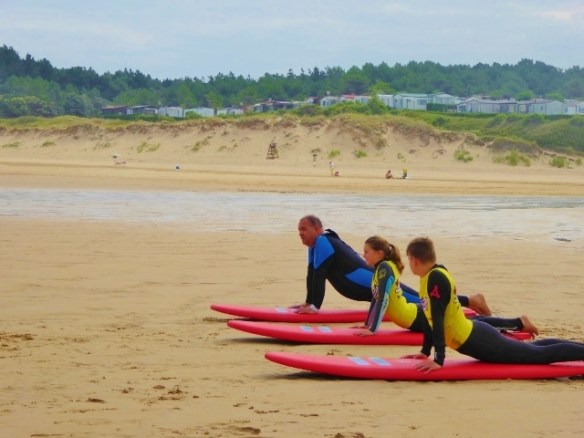 WagonersAbroad surfing in Cantabria Spain. Trying to pop up on the surfboard is easier on land.