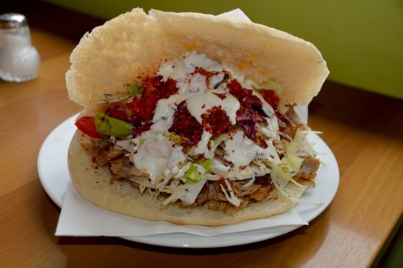 gyroorgyros is a Greek dish made from meat cooked on a vertical rotisserie.Then stuffed into a pita bread and topped with veggies and yogurt sauce.