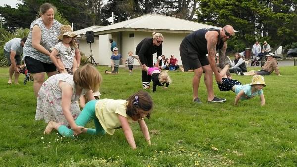 Adults and kids in a wheelbarrow race.