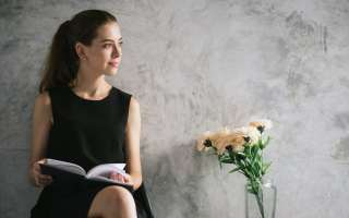 Portrait of a beautiful young woman reading book relaxing in living room