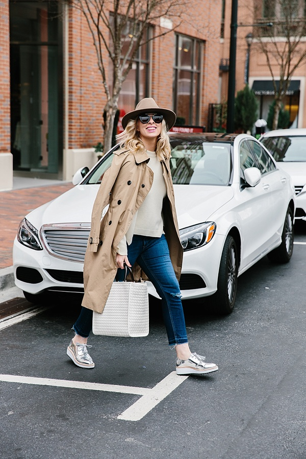 The best travel outfit: trench coat, sweater, stylish sneakers and hat