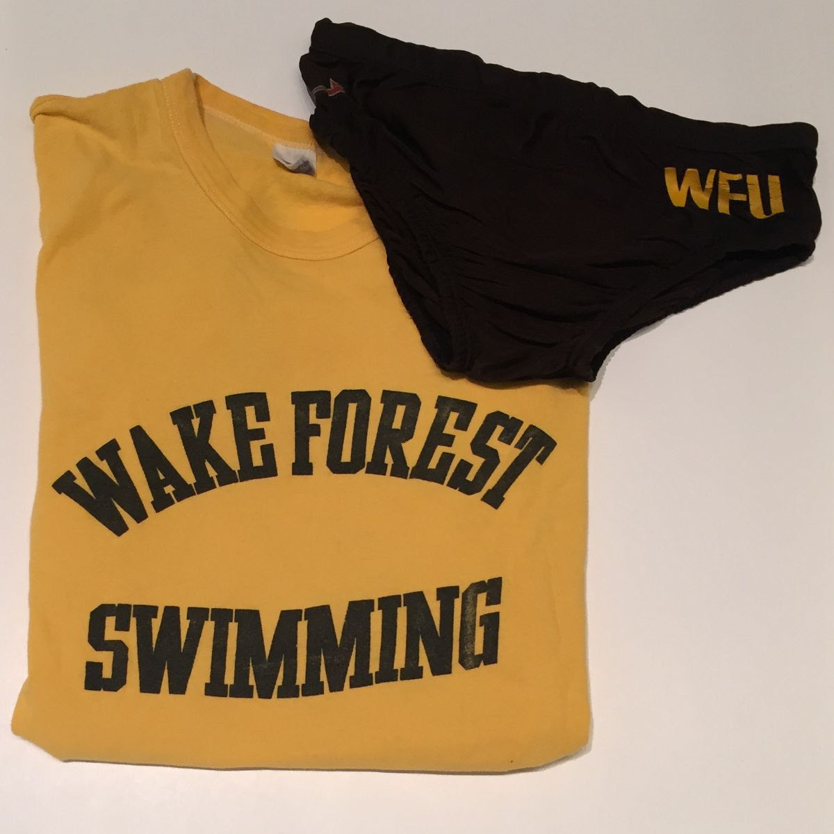 """Photo of gold t-shirt with black text that reads """"Wake Forest Swimming"""" and black speedo with gold """"WFU"""""""
