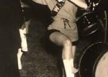 Photograph of majorette with baton, dancing.