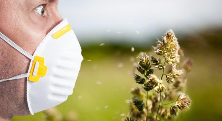 man wearing allergy mask next to pollen