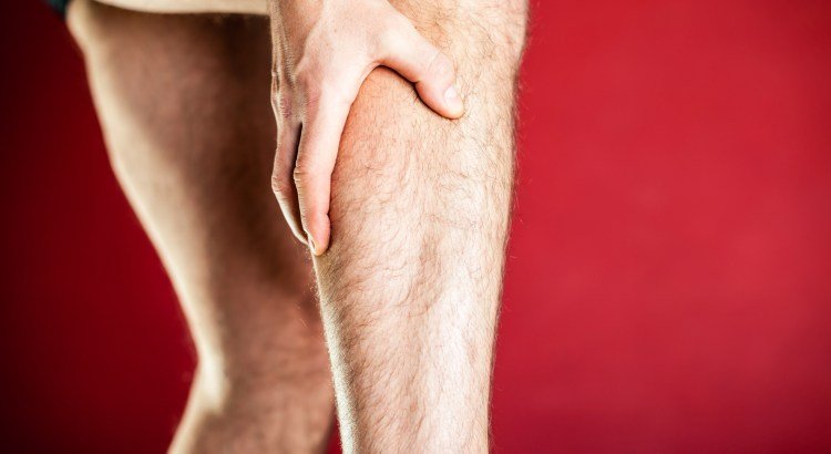 Running physical injury, calf leg pain. Runner sore body after exercising, massage and medical examining, red background