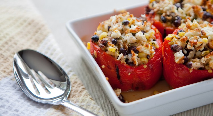 A dish full of roasted peppers stuffed with corn, rice and black beans, sits on a table ready to be served.
