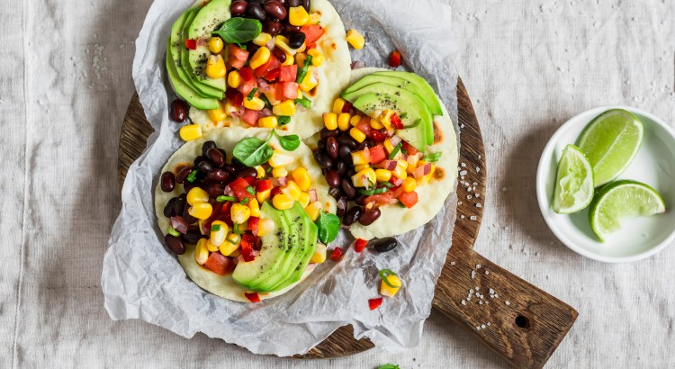 Spicy bean tortillas with corn salsa and avocado  on a rustic cutting board on a dark background. Delicious vegetarian snack