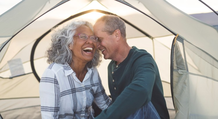 A mixed race senior couple snuggle and flirt. They are camping and are seated in their tent. The door to their tent is unzipped. Light from the setting sun shines through the back of the tent. The couple is laughing. The husband has his eyes closed and is resting his forehead on his wife's temple. The wife is looking off into the distance while she laughs. The couple is dressed in casual clothing and the woman is wearing glasses.