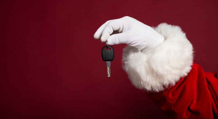 Male hand in white glove and Santa Clause costume holding key on red background, Christmas and New year concept