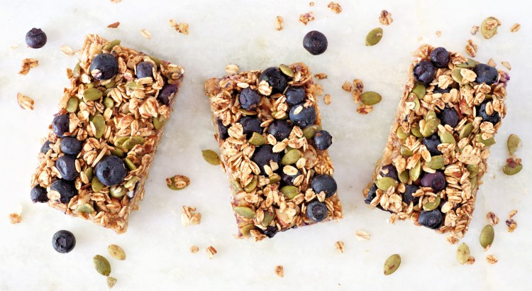Superfood breakfast bars with oats and blueberries, above view on white marble background