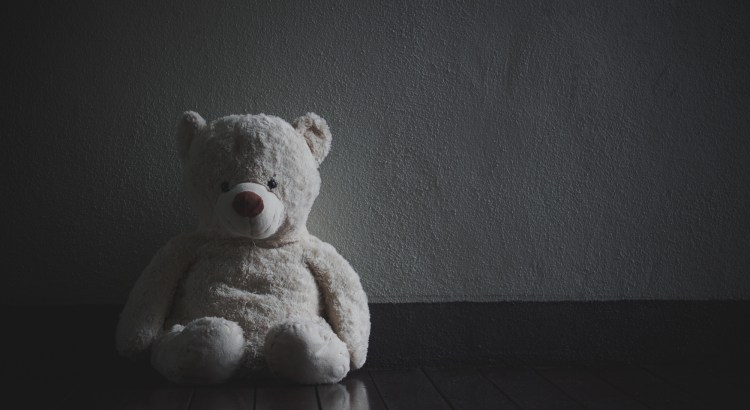 Lonely Teddy Bear Sitting in the dark room (Concept about love)