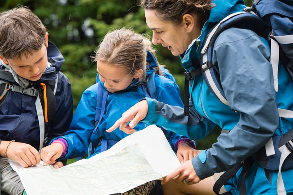 family-looking-at-map-GettyImages-1059380472