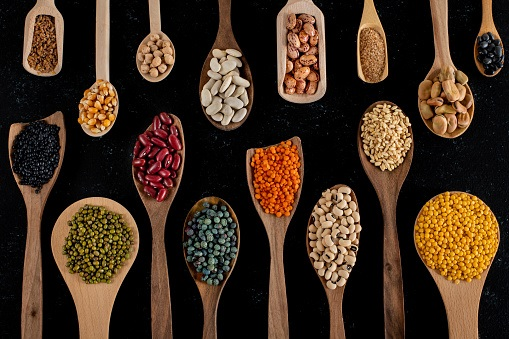 Dried legumes in the wooden spoons.