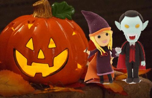 ハロウィンの魔女とドラキュラがかぼちゃランタンの前で記念撮影している画像
